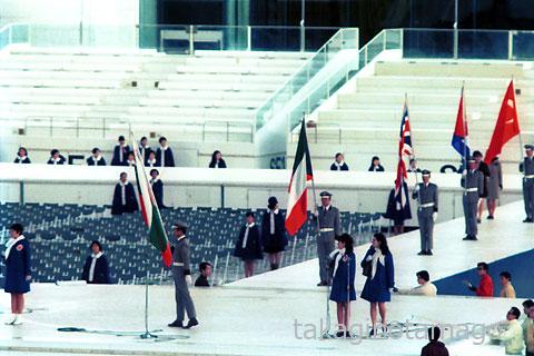 国旗の入場と観客席に立つコンパニオン